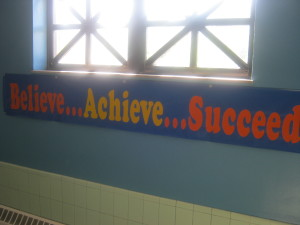 A banner with the words believe, achieve, succeed, hangs to motivate students on their way to class. Photo by Keio Horton.