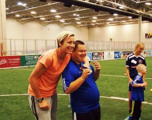Wambach shares a smile and her FIFA medal