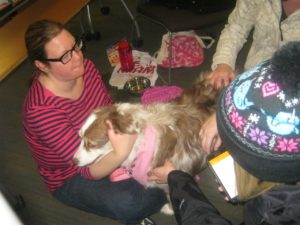 A student hugs a therapy dog in the Library.